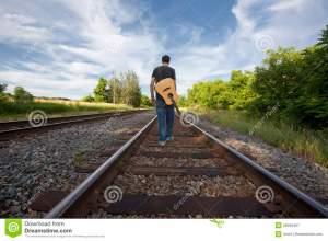 man-walking-rail-road-tracks-guitar-26595407